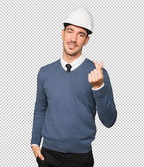 Gelukkig jonge architect die een geldgebaar met zijn hand maakt