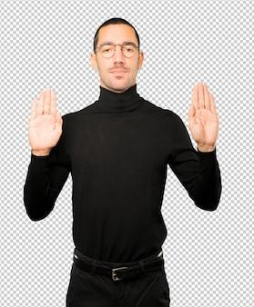 Gelukkig jonge man die een gebaar van stop maakt met zijn handpalm