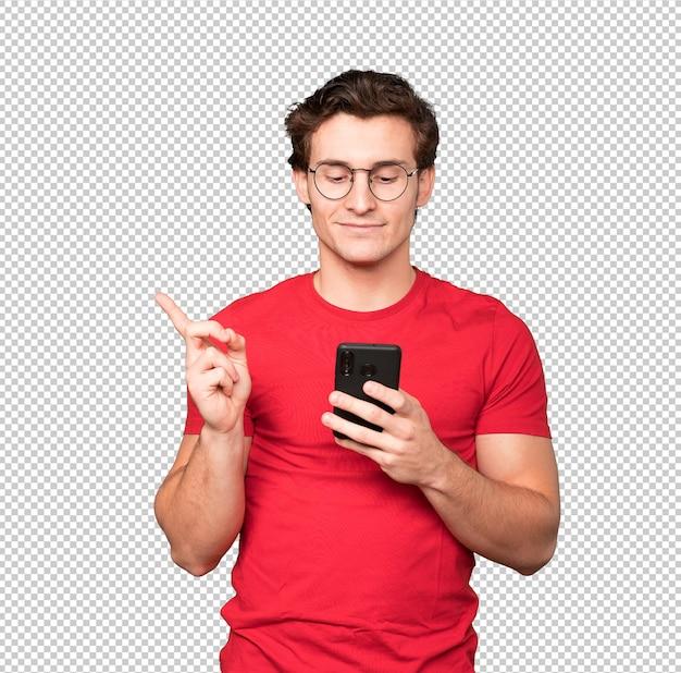 Gelukkig jonge man die omhoog wijst en een mobiele telefoon gebruikt