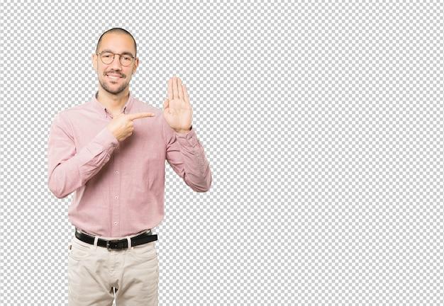 Gelukkig jonge man een gebaar van stop met zijn handpalm maken
