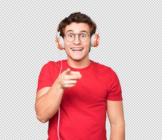 Gelukkig jonge man met koptelefoon en een smartphone en wijst naar jou