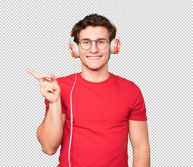 Gelukkig jonge man met koptelefoon en een smartphone en wijst