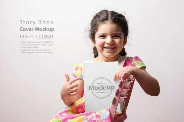 Gelukkig klein meisje wijst naar een verhalenboek met blanco omslag voor haar lichaam