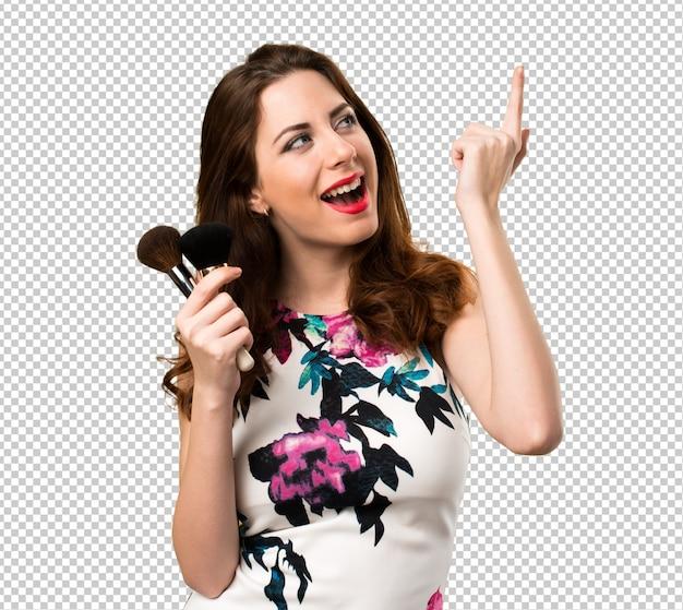 Gelukkig mooi jong meisje met make-upborstel het denken