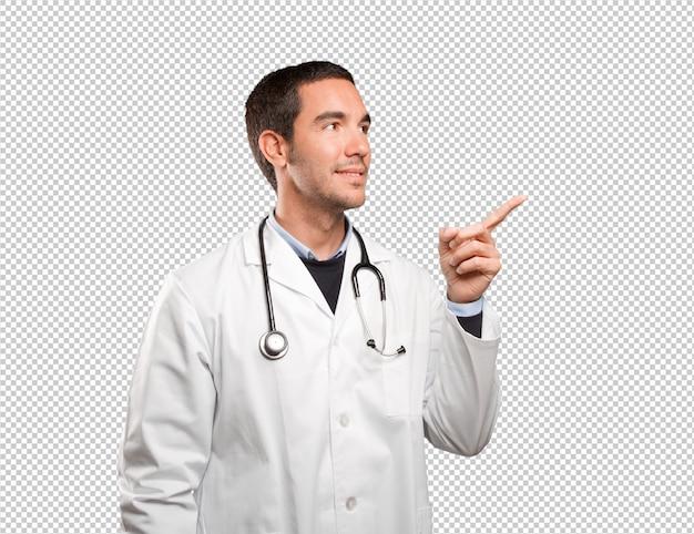 Gelukkige arts die tegen witte achtergrond richt