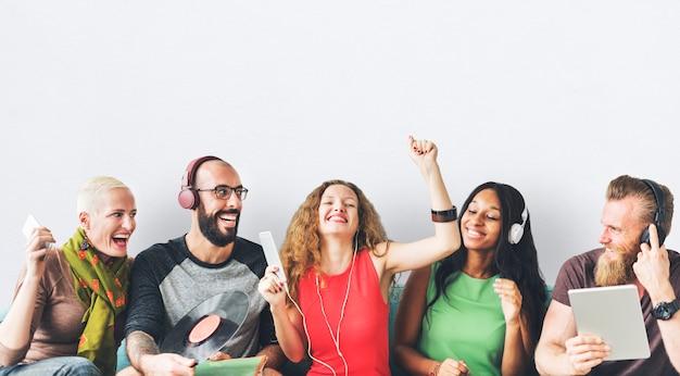 Gelukkige groep vrienden die en aan muziek delen luisteren