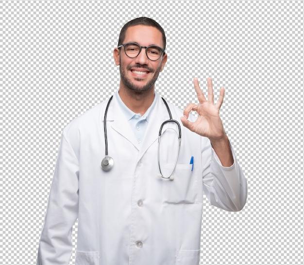 Gelukkige jonge arts met een gebaar van oke