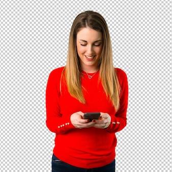 Gelukkige jonge blonde vrouw die aan mobiel spreekt