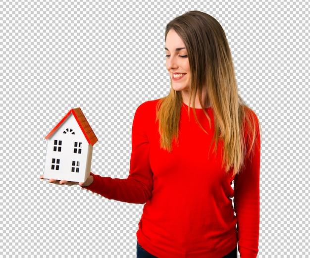 Gelukkige jonge blonde vrouw die een klein huis houdt