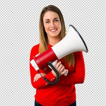 Gelukkige jonge blonde vrouw die een megafoon houdt