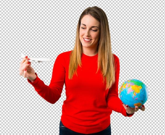 Gelukkige jonge blonde vrouw die een stuk speelgoed vliegtuig houdt