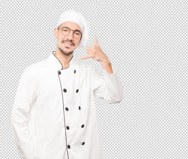 Gelukkige jonge chef-kok die een gebaar maakt van het roepen met de hand