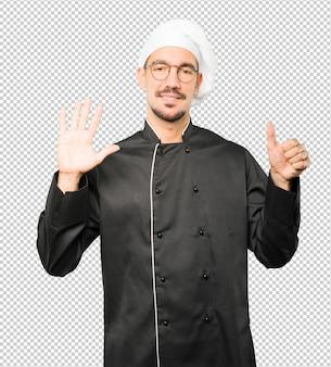 Gelukkige jonge chef-kok die een gebaar nummer zes met zijn handen doet