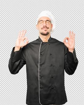 Gelukkige jonge chef-kok die een gebaar van meditatie doet