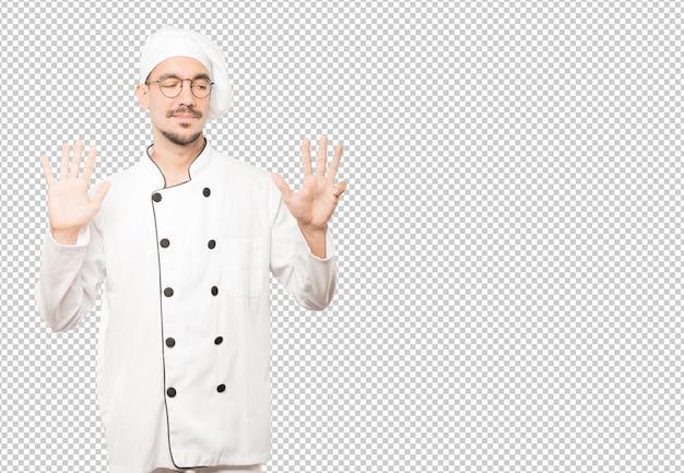 Gelukkige jonge chef-kok die een gebaar van nummer negen met zijn handen doet