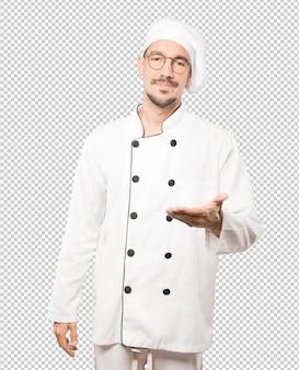 Gelukkige jonge chef-kok die een gebaar van welkom met zijn hand doet