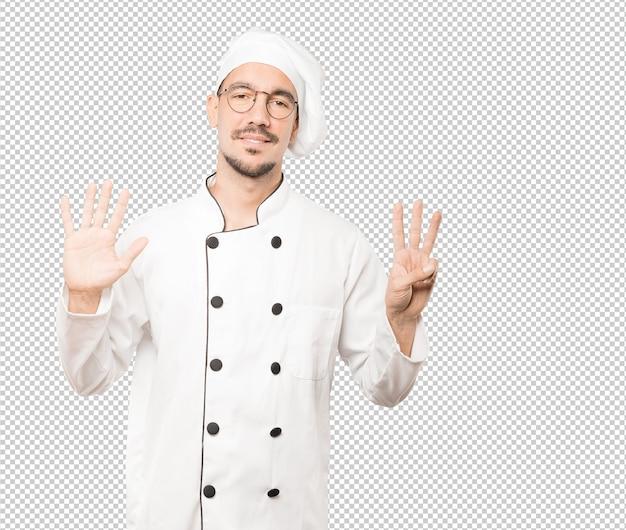 Gelukkige jonge chef-kok die een nummer acht gebaar met zijn handen doet
