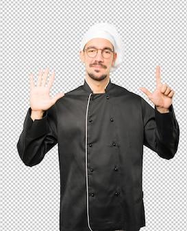 Gelukkige jonge chef-kok die een nummer zeven gebaar met zijn handen doet
