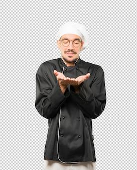Gelukkige jonge chef-kok die iets met zijn hand houdt