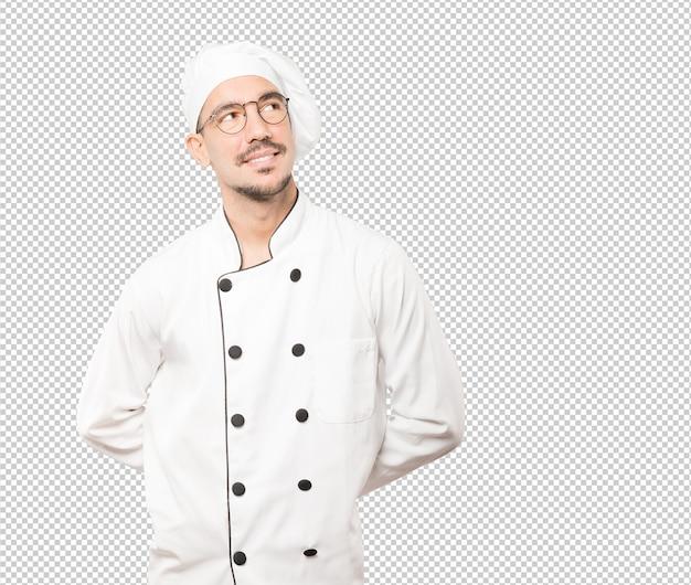 Gelukkige jonge chef-kok die tegen achtergrond kijkt
