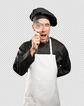 Gelukkige jonge chef-kok met behulp van een vergrootglas
