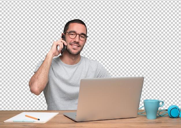 Gelukkige jonge man aan de telefoon en zit aan zijn bureau