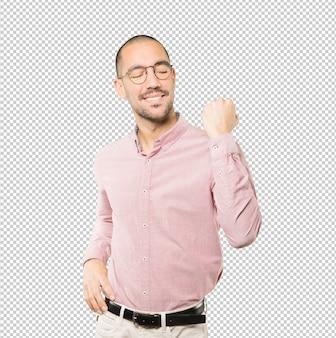 Gelukkige jonge mens die een concurrerend gebaar doet