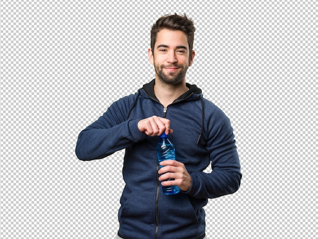 Gelukkige jonge mens die een fles water houdt