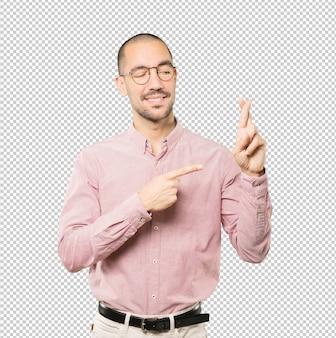 Gelukkige jonge mens die een gekruist vingersgebaar doet