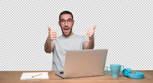 Gelukkige jonge mens die een ok gebaarzitting bij zijn bureau doet