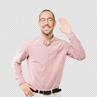 Gelukkige jonge mens die en een gebaar van het proberen om iets te horen glimlachen maken