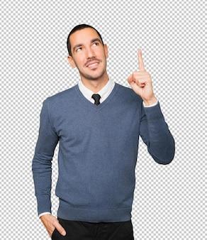 Gelukkige jonge mens die met zijn vinger benadrukt