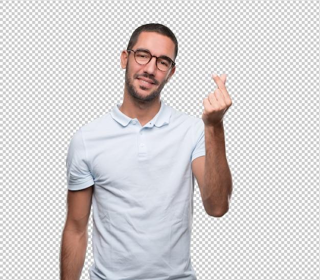 Gelukkige jonge mens met een gebaar van het houden van iets met zijn vingers