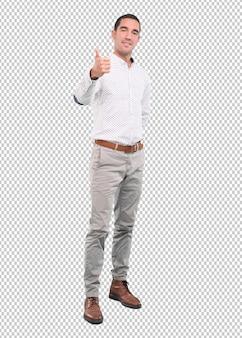 Gelukkige jonge mens met een gebaar van ok - volledig lichaamsschot