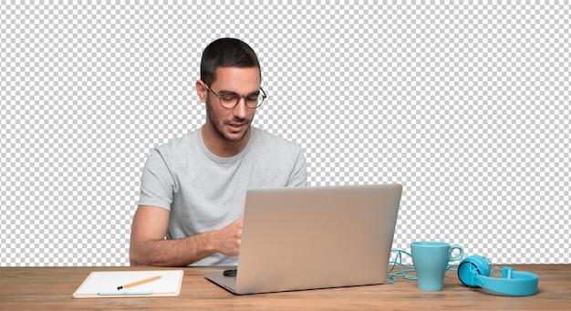 Gelukkige jonge mensenzitting bij zijn bureau en het gebruiken van zijn laptop