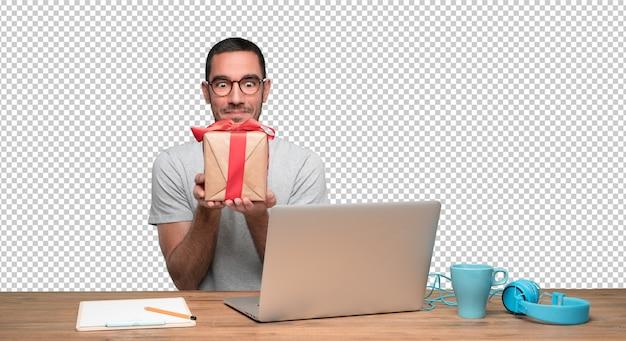 Gelukkige jonge mensenzitting bij zijn bureau en holding een gift