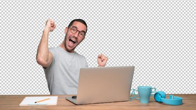 Gelukkige jonge mensenzitting bij zijn bureau met een gebaar van viering