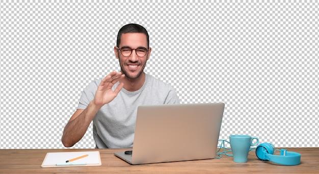 Gelukkige jonge mensenzitting bij zijn bureau