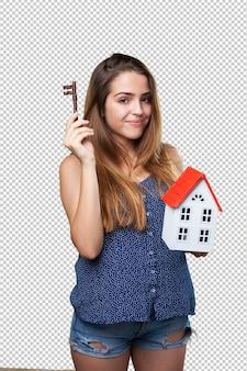 Gelukkige jonge vrouw die een huis en een sleutel houdt