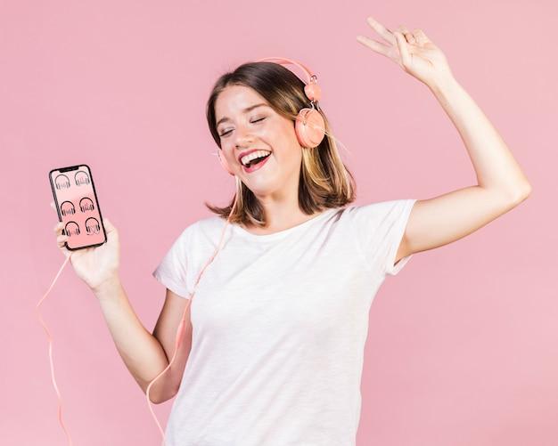Gelukkige jonge vrouw die met hoofdtelefoons een cellphonemodel houdt