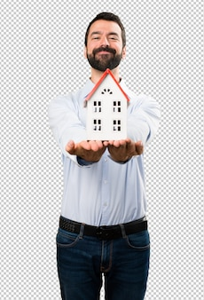 Gelukkige knappe mens die met baard een klein huis houdt