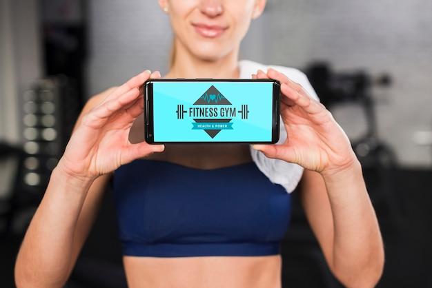 Gelukkige sportieve vrouw die smartphonemodel voorstelt