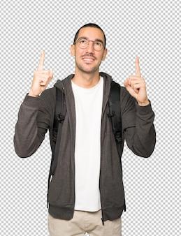 Gelukkige student die met zijn vinger benadrukt