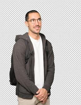 Gelukkige student die tegen achtergrond kijkt