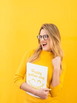 Gelukkige vrouw met geel conceptenmodel