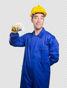 Gelukkige werkman die zijn vuist op witte achtergrond toont