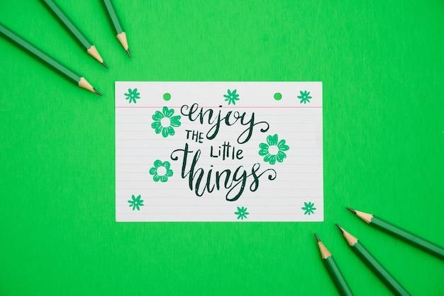 Geniet van het kleine citaat op bloemen witboek en groene achtergrond