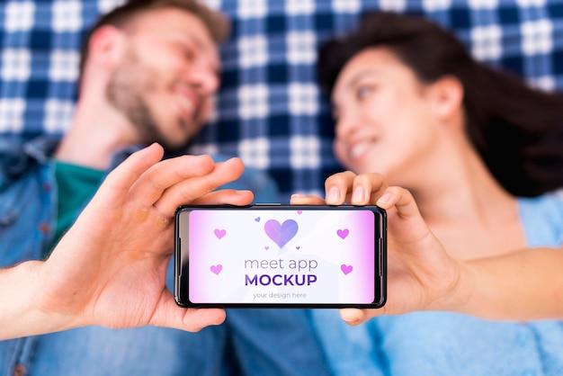 Gente borrosa sosteniendo la maqueta de la aplicación meet en el teléfono móvil