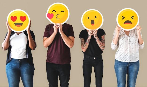 Gente diversa cubierta de emoticones
