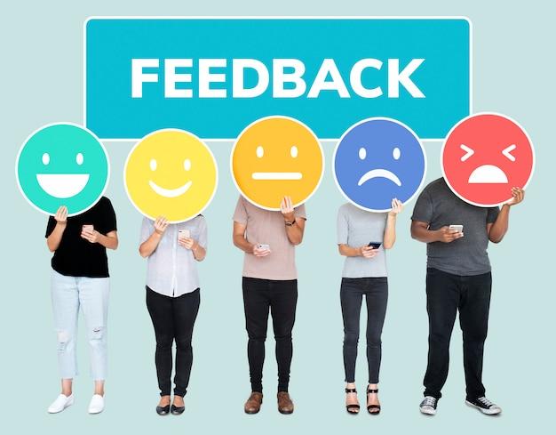 Gente que muestra emoticonos de evaluación de comentarios de clientes.